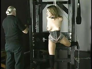 Bondman acquires rope around wrists teats clamped and ball gag in her throat